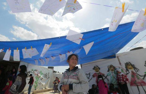 فتاة أسفل رسومات لأطفال سوريين في مخيم للاجئين (بر إلياس- البقاع اللبناني)