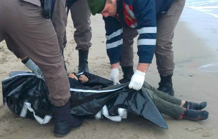 الشرطة التركية تسحب جثة لاجئ على الشاطئ بعد غرق قاربهم خلال رحلتهم إلى أوروبا - 5 كانون الثاني 2015 (الأناضول)