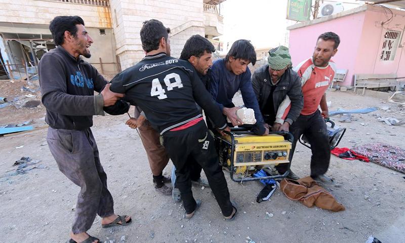 أشخاص يتنازعون على نهب مولدة كهربائية في مدينة الشدادي - 26 شباط 2016 (رويترز)