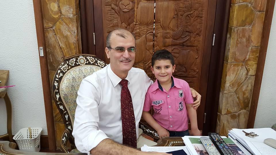 """القائم بالأعمال في مكتبه، مع طفل سوري اسمه جعفر ينوي التوجه إلى السفارة الألمانية في تنزانيا من أجل """"لم الشمل""""."""