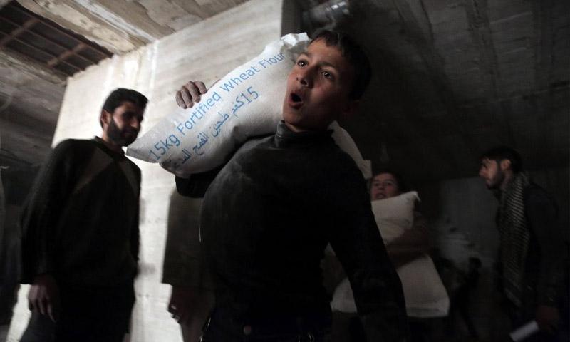 طفل يحمل كيس طحين في كفربطنا بريف دمشق (AFP)