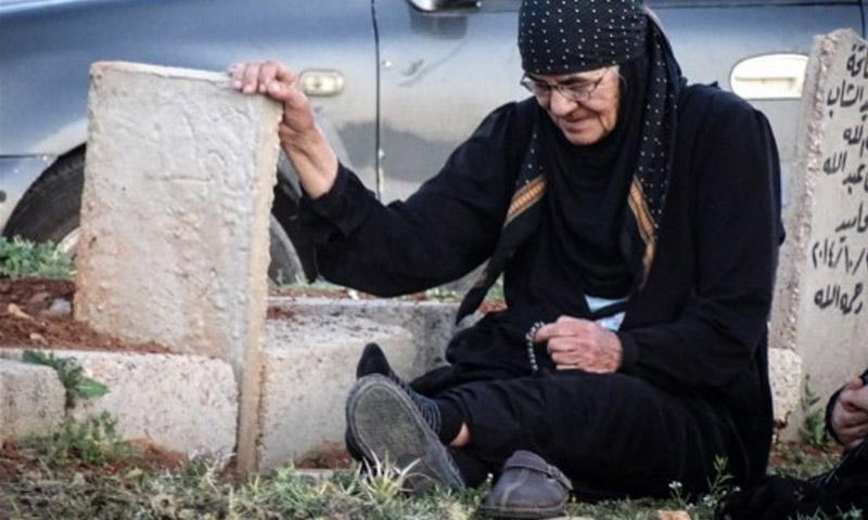 امرأة مسنة تجلس عند قبر ابنها الذي قتل في اشتباكات ضد قوات الأسد في درعا 7 نيسان 2016 (AFP)
