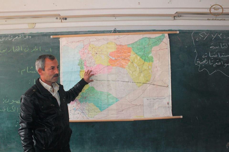 مدرس يشرح للتلاميذ خلال حصة جغرافيا في مدرسة بحماة، عنب بلدي.