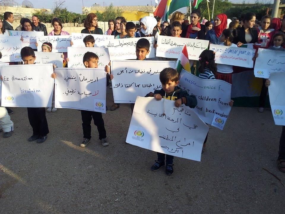 أطفال يحملون لافتات في مظاهرة بمدينة عامودا، عنب بلدي.