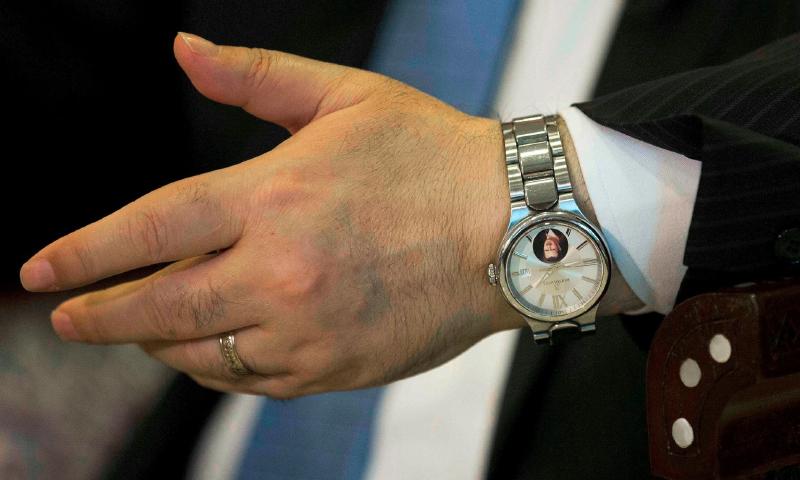 """وزير الخارجية فيصل المقداد يرتدي ساعة تحمل صورة الأسد خلال مقابلة مع وكالة """"أسوشييتد برس"""" - 13 نيسان 2016"""