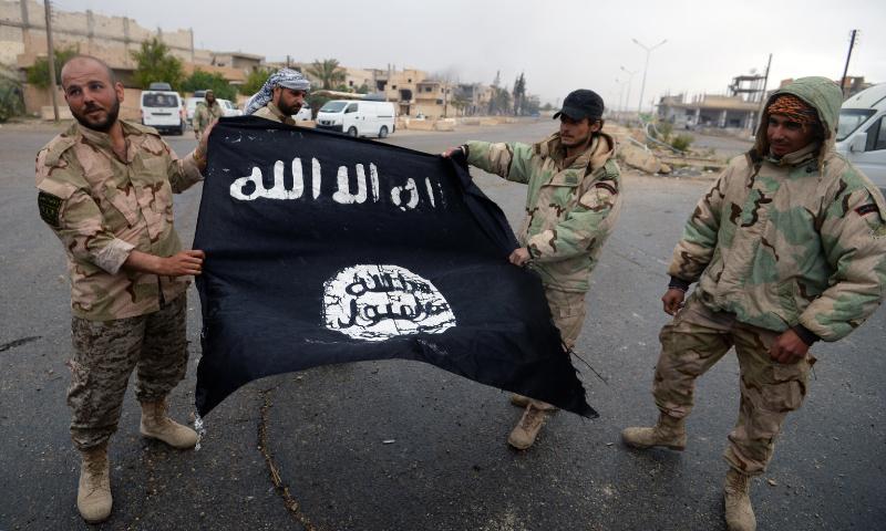 """قوات الأسد تحمل علم تنظيم """"الدولة"""" في تدمر - 28 آذار 2017 (AFP)"""