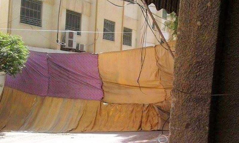 """شوادر منصوبة في شارع المدارس داخل مخيم اليرموك لتفادي القناصات، السبت 9 نيسان، المصدر: صفحة """"اليرموك تايمز""""."""