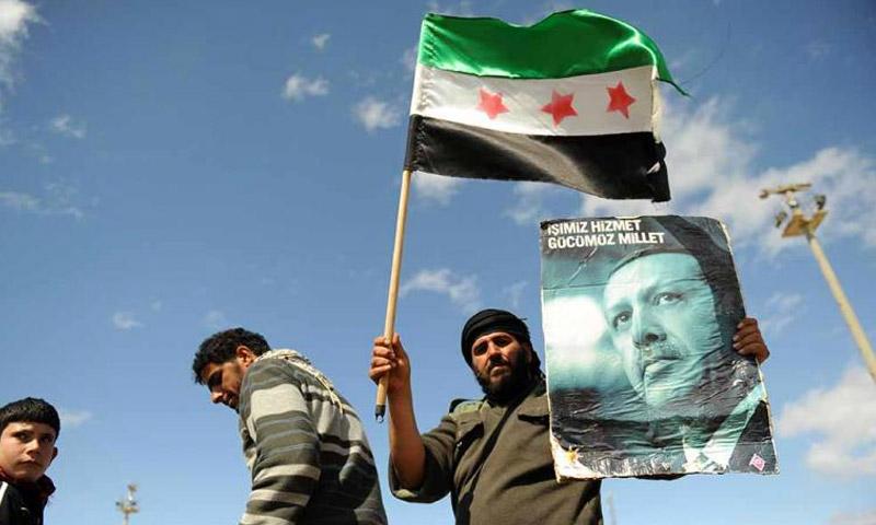 لاجئ سوري يحمل علم الثورة السورية وصورة أردوغان في أنطاكيا آذار 2012 (جيتي)