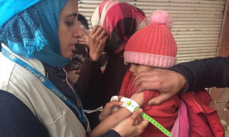 متوطعة في اليونيسيف تفحص طفلة في مضايا - كانون الثاني 2016 (AFP)