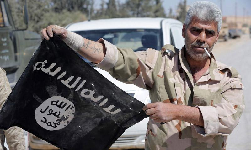 """مقاتل في قوات الأسد يحمل راية تنظيم """"الدولة"""" قبل حرقها في تدمر - 4 نيسان 2016 (AFP)"""