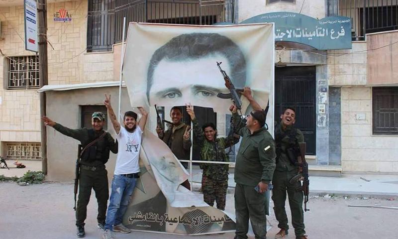 إزالة صورة بشار الأسد من مبنى التامينات الاجتماعية في مدينة القامشلي، الأربعاء 20 نيسان.