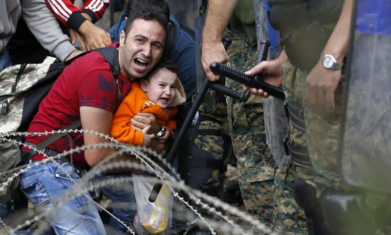 لاجئ سوري في ايدوميني شمال اليونان بينما تمنعه الشرطة من الوصول إلى محطة القطارات (AP)