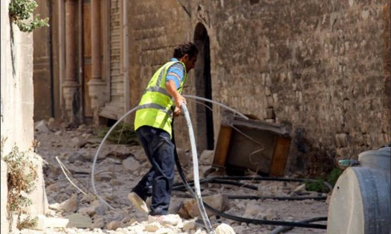 فريق تقني يحاول إعادة الكهرباء إلى أحياء حلب القديمة في أيلول 2014 (مصطفى سلطان - AFP)