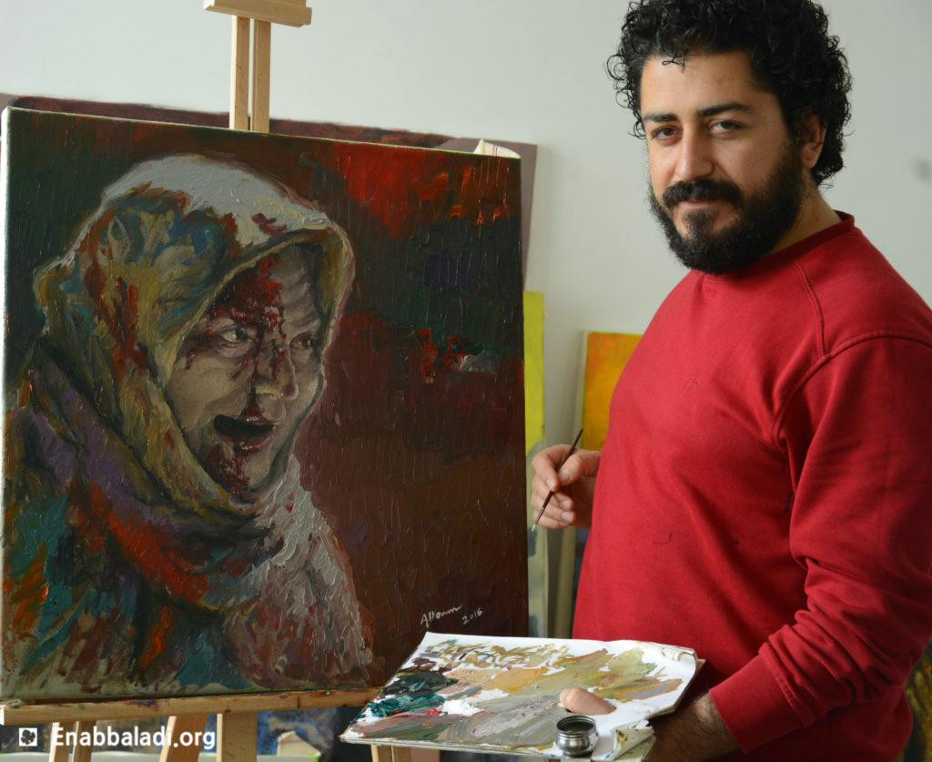 الفنان السوري حسام علوم مع لوحته (عنب بلدي)