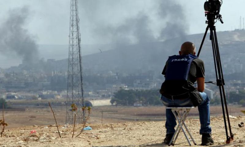 مصور يرصد الدخان المتصاعد من عين العرب (كوباني) - تشرين الأول 2014 (AFP)