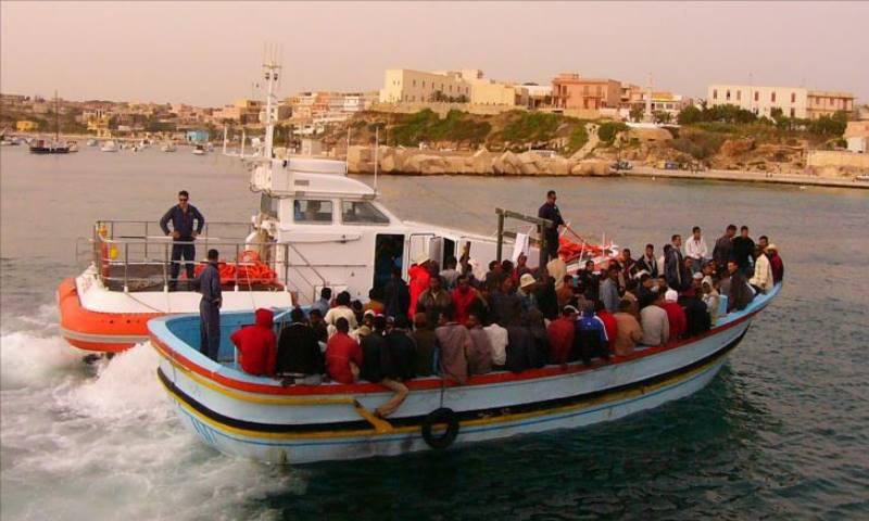 لاجئون قادمون من ليبيا إلى جزيرة لامبيدوزا برفقة خفر السواحل الإيطالي (الجزيرة)