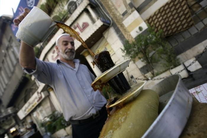"""بائع سوري يصنع مشروب """"عرق سوس"""" في حي الميداني- رمضان 2011 (AFP)"""