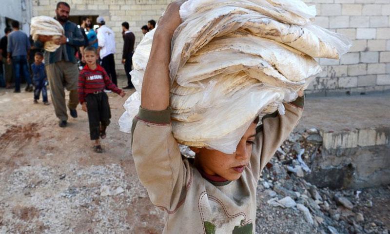 صبي سوري يحمل الخبز في محافظة حلب 2012. (AFP)