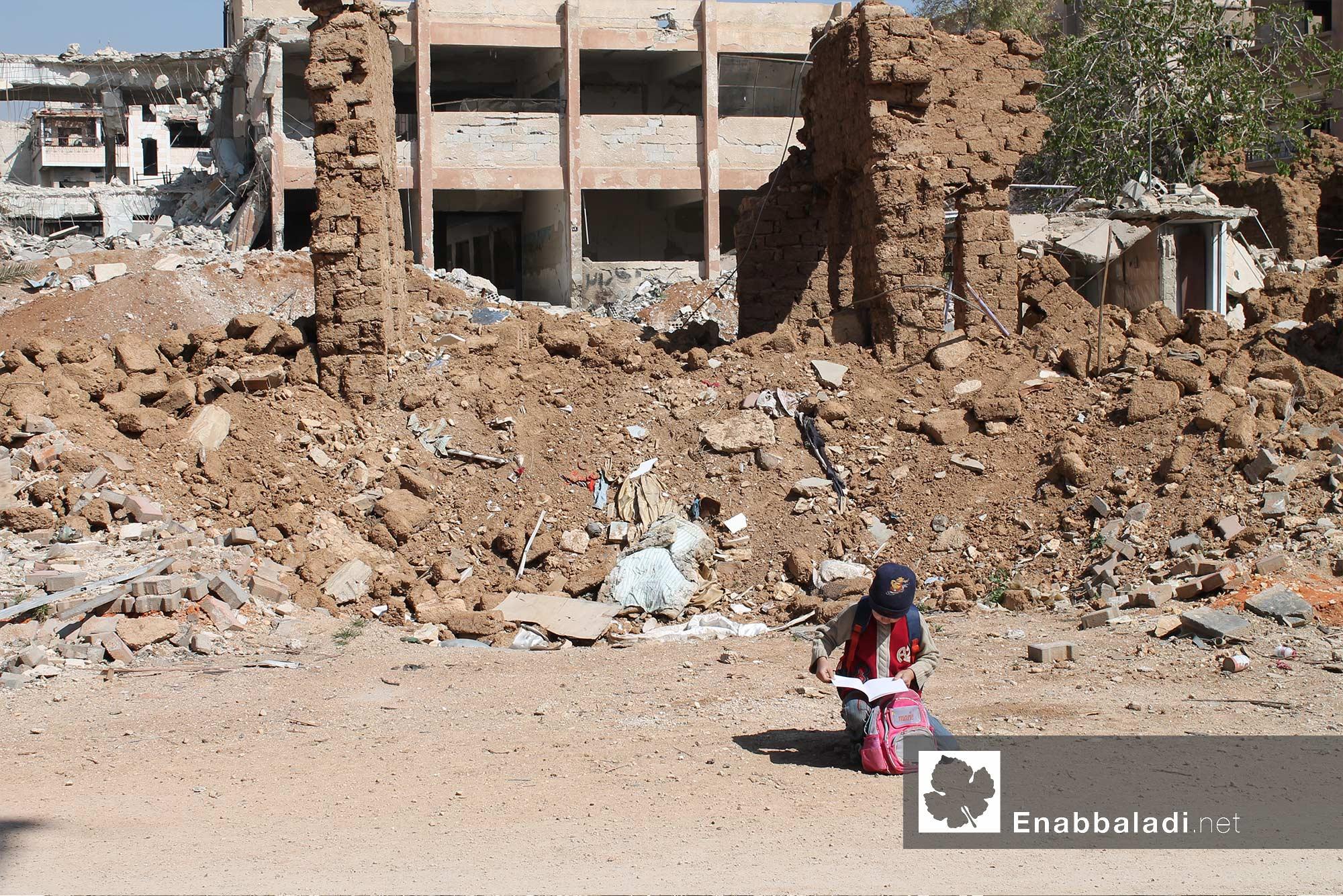 طفلة تقرأ أمام مدرسة مهدمة جراء القصف على داريا بريف دمشق- 30 آذار 2016 - (عنب بلدي)