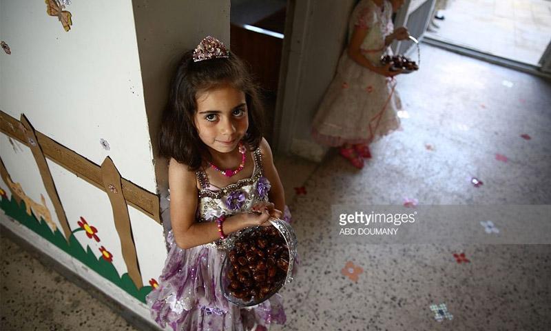 """طفلة سورية تقدم التمور في احتفالٍ لمدرسة """"سيف الدولة"""" في مدينة دوما - 25 أيار 2016 (عبد دوماني - AFP)"""