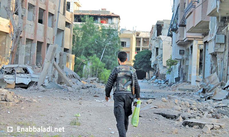 مقاتل في مدينة داريا بريف دمشق، وأمامه شجيرات خضراء بقيت في داريا (عنب بلدي)