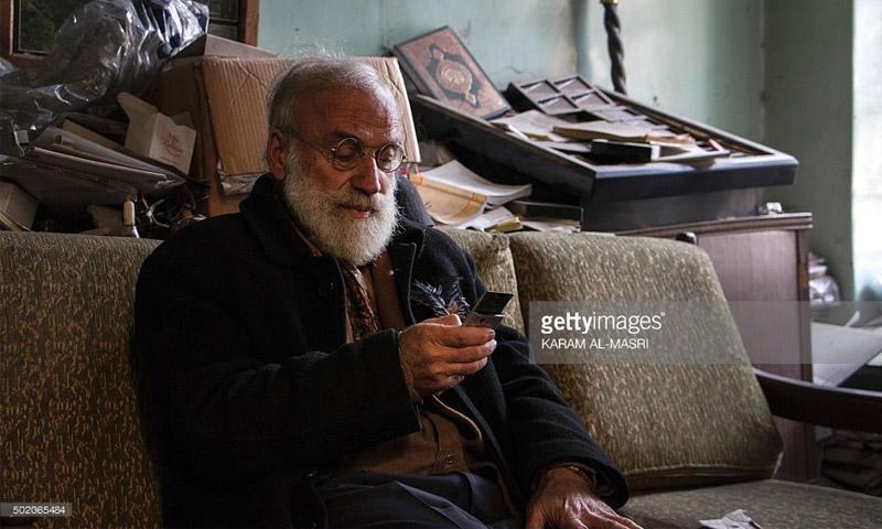 أبو عمر جامع تحف كلاسيكية (69 عامًا) يحمل هاتفه في حلب (كرم المصري - جيتي)