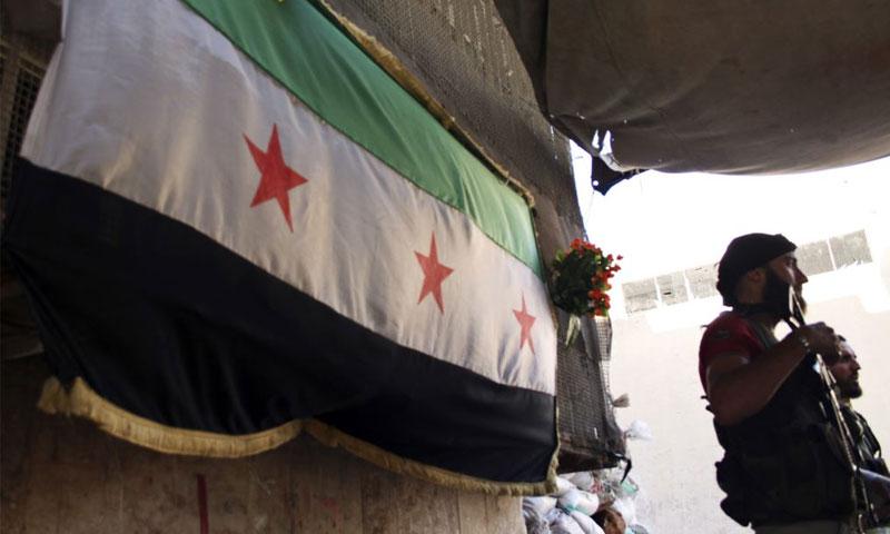 مقاتل من الجيش السوري الحر يقف أمام علم الجيش الحر- بستان القصر -حلب 2013 (رويترز)