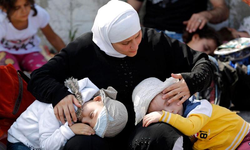 لاجئة سورية تحضن ولديها في تركيا (إنترنت)