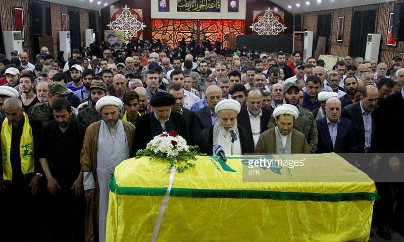 """الصلاة على القيادي في حزب الله، خليل علي السيد حسن، في قاعة """"الحوراء زينب""""، قتل في ريف حلب الجنوبي (جيتي - AFP)."""