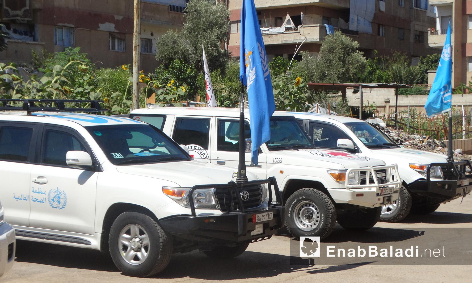 سيارات الوفد المرافق لقافلة  المساعدات داخل حي الوعر في حمص - الخميس 14 تموز (عنب بلدي)