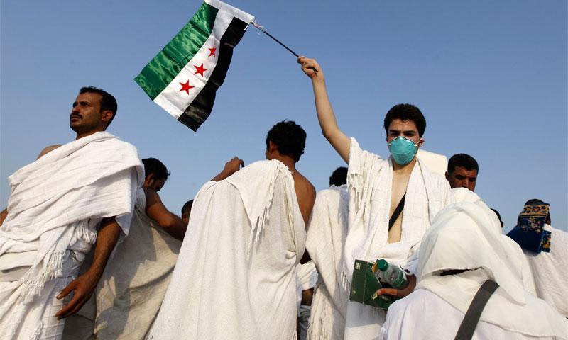 حاج سوري يرفع علم الثور السورية في عرفات