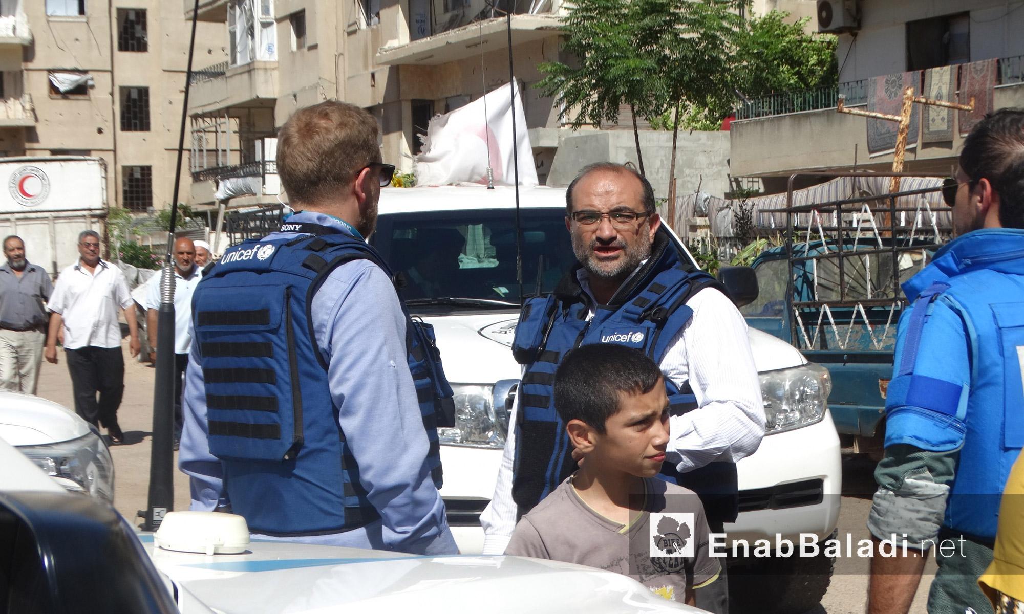الوفد المرافق لقافلة  المساعدات داخل حي الوعر في حمص - الخميس 14 تموز (عنب بلدي)