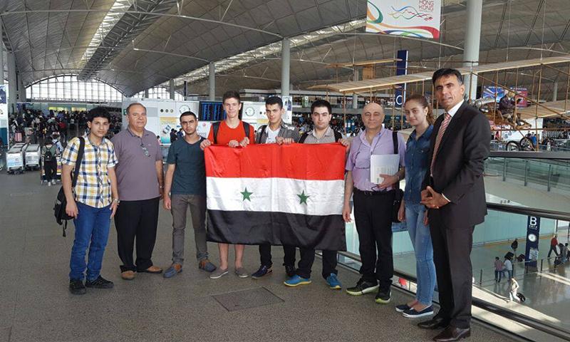 نجل الأسد إلى جانب فريق الأولمبياد السوري للرياضيات في هونغ كونغ (صفحة رئاسة الجمهورية السورية)