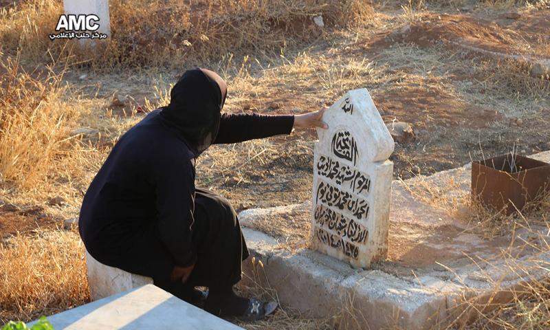 امرأة تجلس إلى جانب قبر شهيد في مقبرة مساكن هنانو - 6 تموز 2016 (مركز حلب الإعلامي)