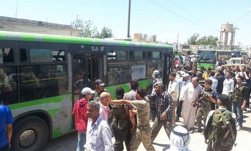 مقاتلو وأهالي قزحل قرب حافلات نقلهم إلى ريف حمص الشمالي - السبت 16 تموز (ناشطون)