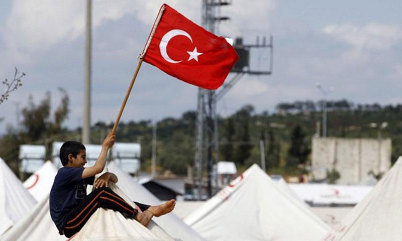 طفل سوري يجلس على خيمة ويحمل علم تركيا في مخيم للاجئين في تركيا (إنترنت)