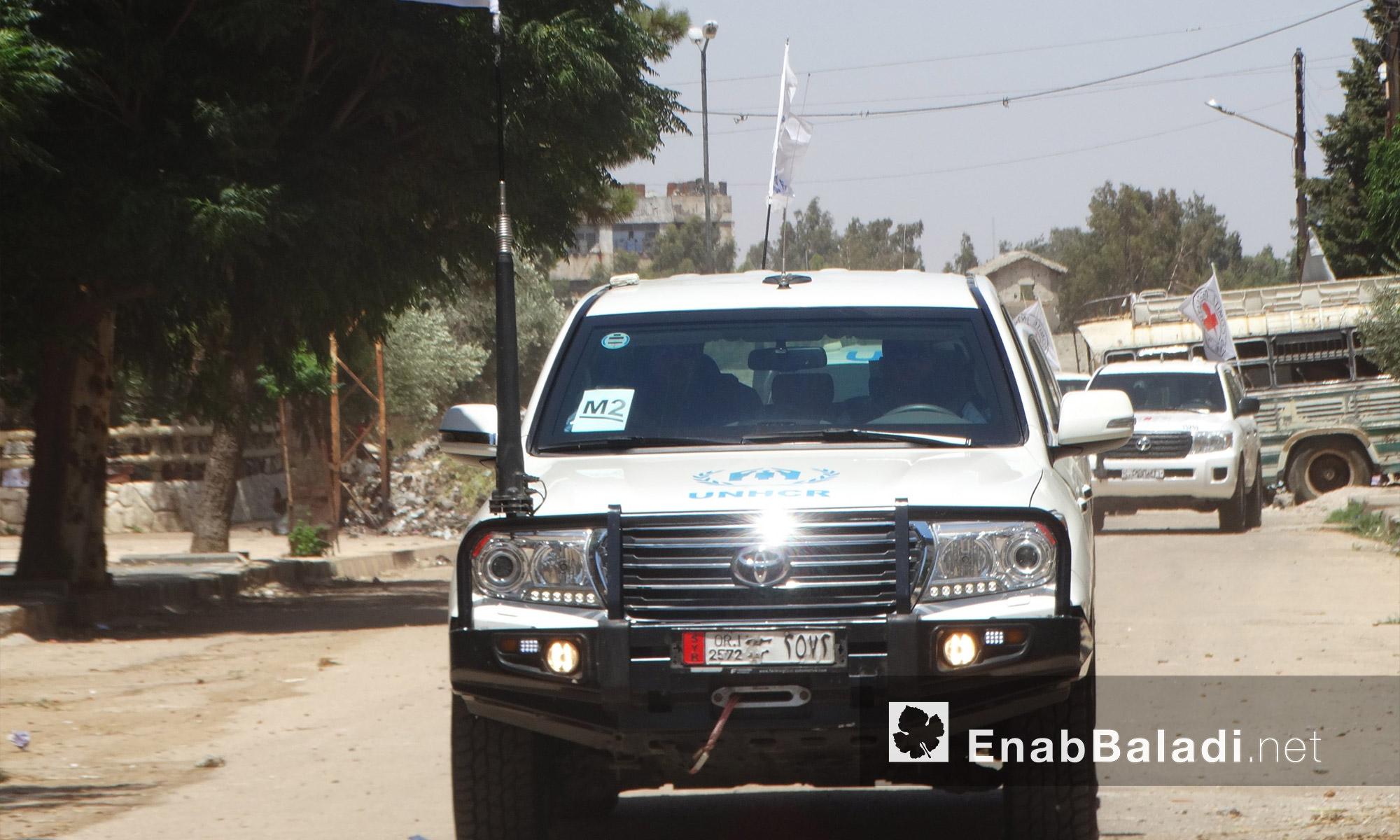 سيارات قافلة المساعدات الغذائية في حي الوعر بحمص - الاثنين 18 تموز (عنب بلدي)