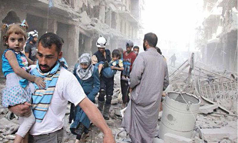رجال الدفاع المدني ومواطنون يسيرون وسط الركام إثر الغارات الجوية على حلب (AMC)
