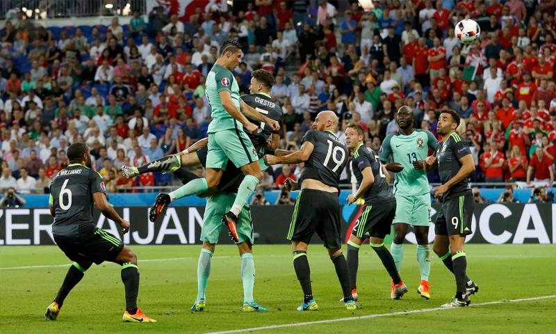 كريستيانور رونالدو أثناء توجيه كرة الهدف الأول للبرتغال والدفاع الويلزي يكتفي بالمشاهدة (رويترز)