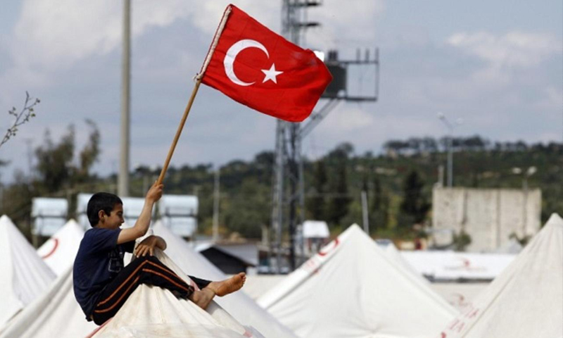 طفل سوري يرفع علم تركيا فوق المخيم (انترنت)
