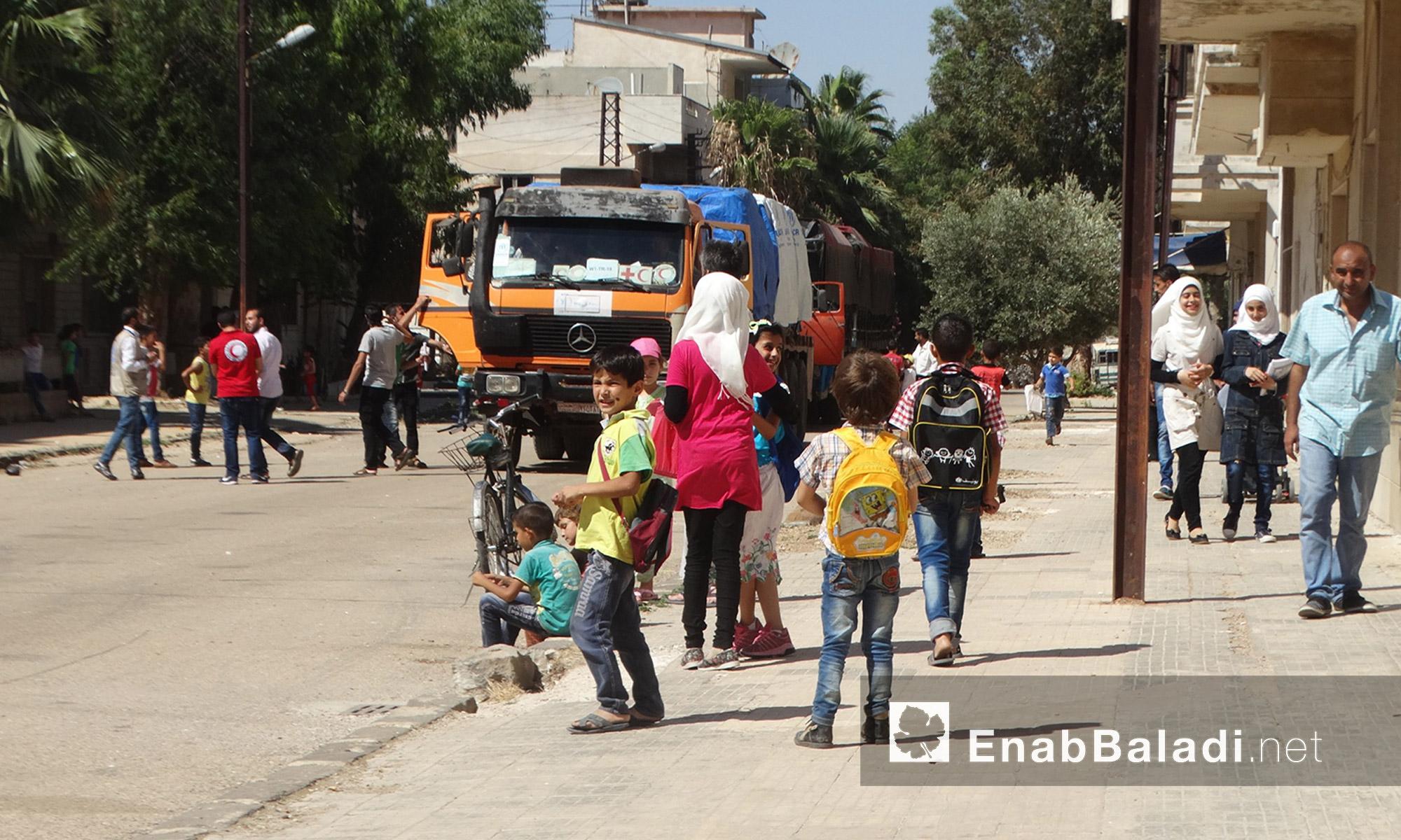 أطفال وأهالي الوعر أثناء دخول قافلة  المساعدات - الخميس 14 تموز (عنب بلدي)