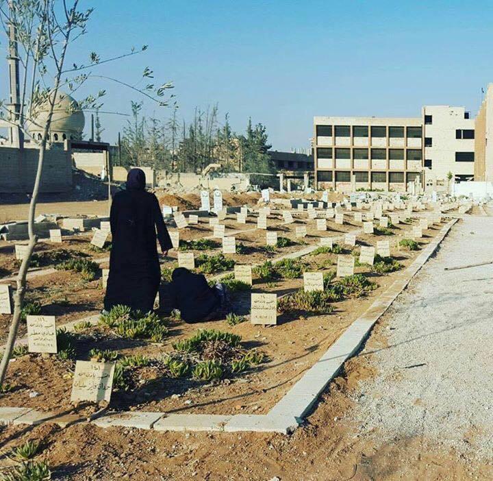 نساء يودعن قبور أبنائهن في داريا (فيس بوك)