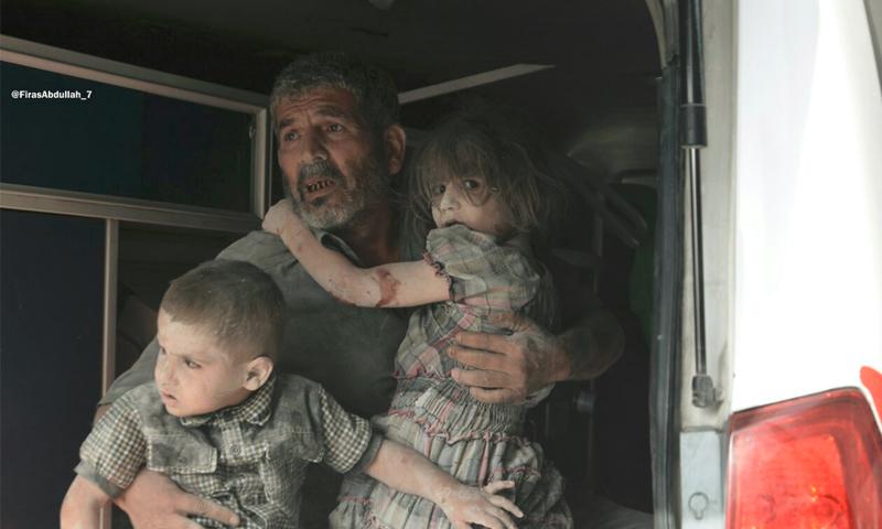 رجل يحتضن طفليه عقب الغارات على مدينة دوما - الثلاثاء 23 آب (ناشطون)