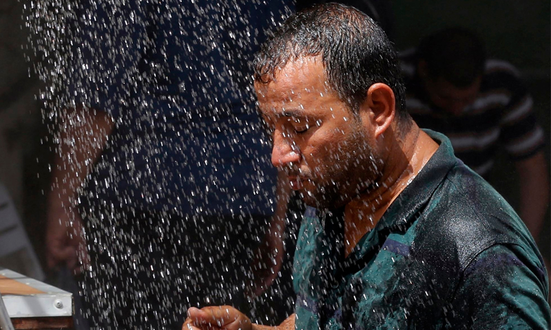 مواطن عراقي يتظلّل برذاذ ماء بسبب الحر (إنترنت)