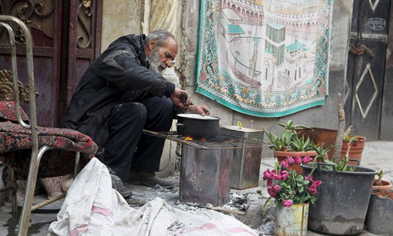 رجل يطبخ باستخدام الحطب في حلب 22 كانون الثاني (روتيرز)
