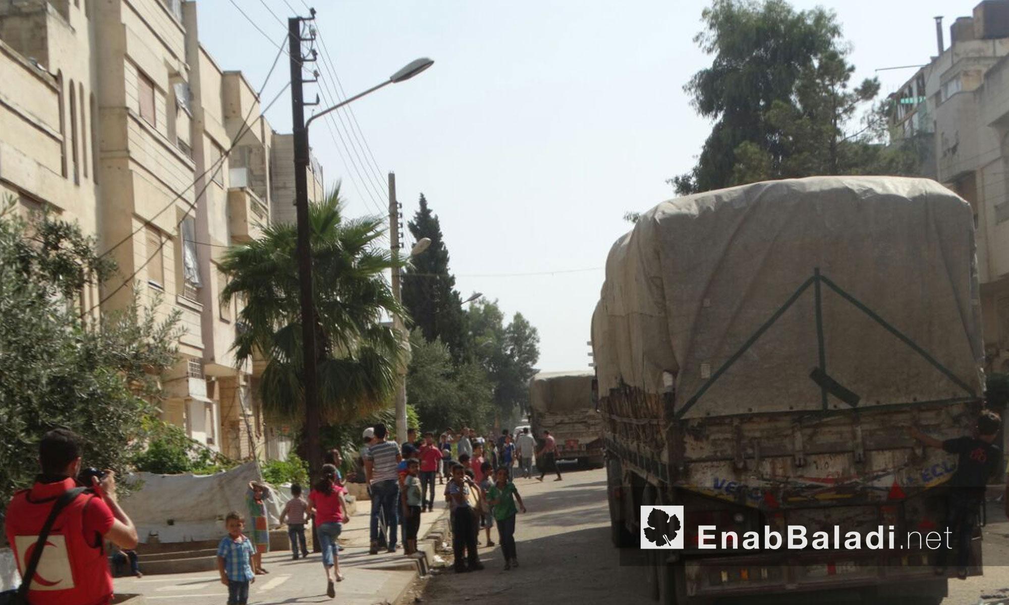 شاحنة تحوي أكياس ضمن  قافلة المساعدات الإنسانية داخل حي الوعر المحاصر - الخميس 25 آب (عنب بلدي)