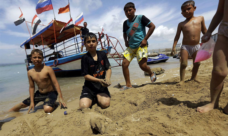 أطفال سوريون على أحد شواطئ اللاذقية أيار 2014 (AFP)