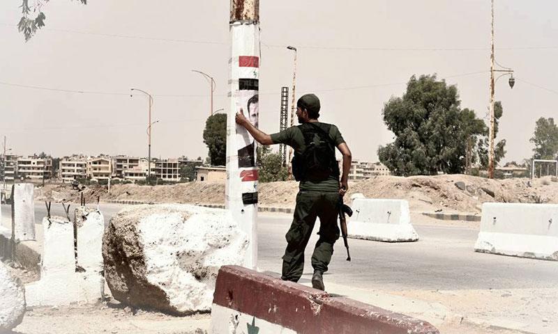 """مقاتل كردي يمزق صورة بشار الأسد من أمام فرع """"الأمن الجنائي"""" في مدينة الحسكة- الاثنين 22 آب (تويتر)"""