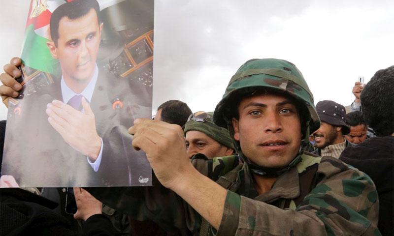 عنصر من قوات الأسد يحمل صورة بشار الأسد في ريف دمشق شباط 2016