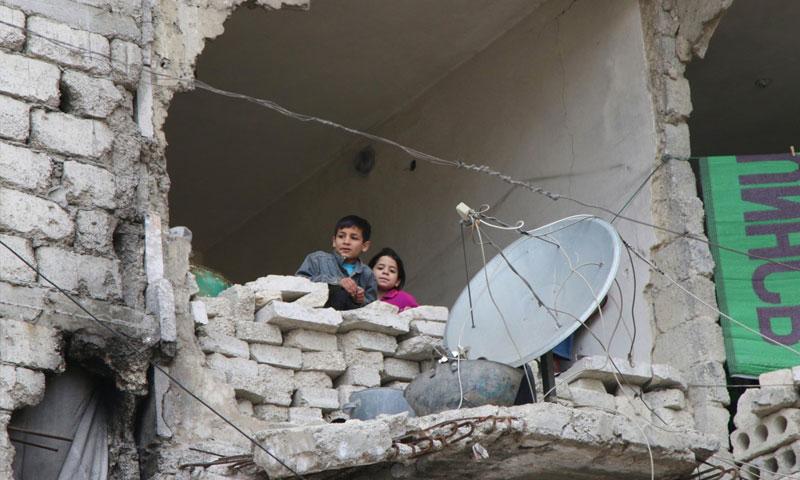 طفلان يطلان من منزلٍ مهدّم في حلب - شباط 2016 (AP)